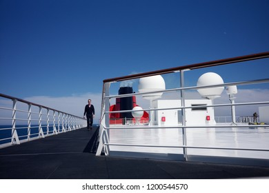 NORTH ATLANTIC OCEAN, INTERNATIONAL WATERS - JULY 19, 2018: man walking on the top deck of the Queen Mary 2, one of the most famous transatlantic cruise liners in the world.