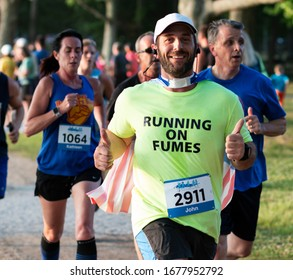 North Babylon, New York, USA - 8 July 2019: Runner racing a 5K at a State Park gives two thumbs up and is wearing a cape while running a race.