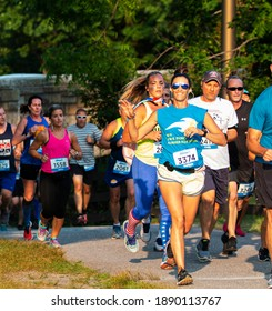 North Babylon, New York, USA - 8 July 2019: A femlae runner is waving and smiling for the camera while running a 5K as she enters bright sunshine in a crowded race.