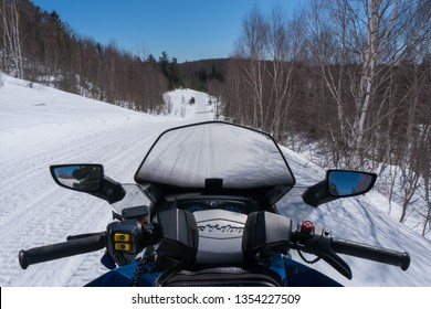 NORTH BAY, ONTARIO - MARCH 25, 2019: View from the Front Seat of a Snowmobile, looking forward through and over the windshield, to the trail ahead. Conecpt