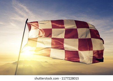 North Brabant province of Netherlands flag textile cloth fabric waving on the top sunrise mist fog