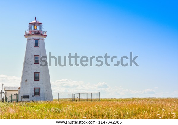 The North Cape Lighthouse with yellow grasses field under the blue sky in Prince Edward Island, Canada.