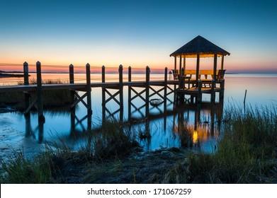North Carolina coastal gazebo stretches into Pamlico Sound during a summer sunset