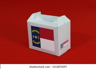 North Carolina flag on white box with barcode and the color of state flag on red background. The concept of export trading from North Carolina, paper packaging for put products.