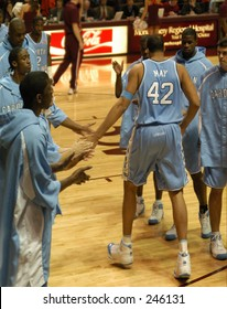 North Carolina men's basketball star Sean May is introduced at a recent game as he slaps hands with teammates