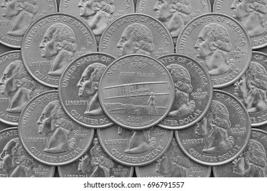 North Carolina State and coins of USA. Pile of the US quarter coins with George Washington and on the top a quarter of North Carolina State.