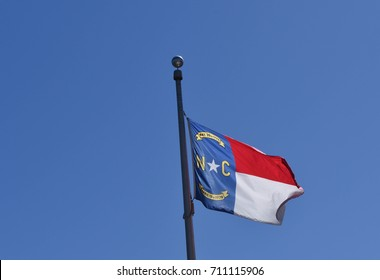 North Carolina state flag with a clear blue sky background