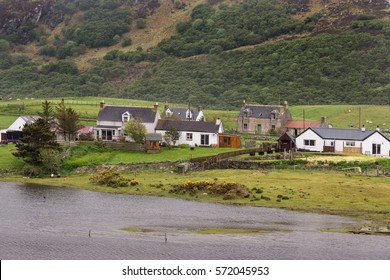 North Coast, Scotland - June 6, 2012: A handful of houses stand together along the Naver River on a green landscape with the slope of rough, brown and green mountain. Houses add whites and reds.