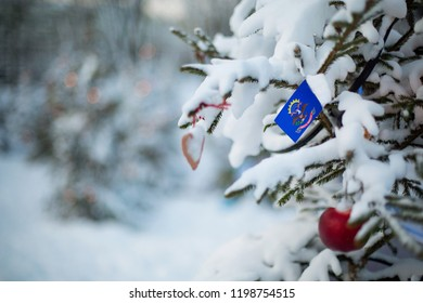 North Dakota state flag. Christmas background outdoor. Christmas tree covered with snow and decorations and North Dakota flag. New Year / Christmas holiday greeting card.