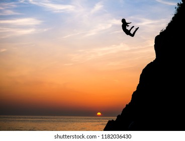 NORTH DEVON, ENGLAND - JULY 12, 2016: Cliff Jumping into the Ocean at Sunset in barricane beach