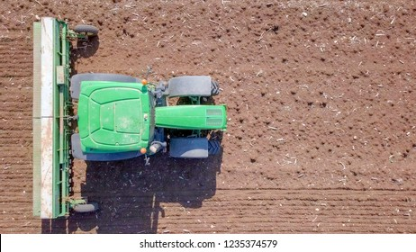 North district, Israel - November 10, 2018: Green Tractor cultivating and seeding a dry field - Top down aerial image.