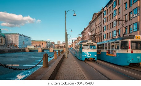 North European city life. Gothenburg, Sweden - April 2, 2013: Blue old electric trams at a street by a canal, in the center of Goteborg, important Scandinavian city of Sweden.