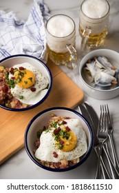 Das norddeutsche Hamburger Labskaus ist eine Delikatesse mit Corned Beef, Kartoffeln, Zuckerrüben, gepickten Cornflakes, frittiertem Ei, Hering und Bier auf dem Marmortisch.