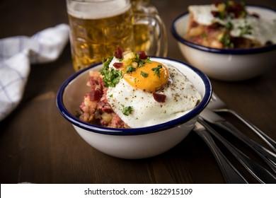 Das norddeutsche Hamburger Labskaus ist eine Delikatesse mit Cornelrinder, Kartoffeln, Rüben, gepickten Cornflakes, frittiertem Ei, Hering und Bier auf Holztisch.