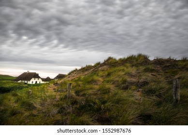 North Germany scenery with Frisian house, high grass on hills and barbed wire fence, on Sylt island, at North Sea, Germany. Grassy dune landscape.