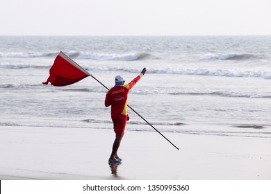North Goa, Arambol, Mandrem / India - December 2018:Men rescuers walk along the shore in red clothes, whistle in the whistle, warn of danger in the sea and expel people from the sea