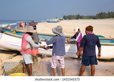 North Goa, Arambol, Mandrem / India - December 2018:   Indian boats and fishermen,  Tourists buy seafood from fishermen on the beach