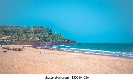 North Goa, India Candolim beach with Aguada fort in the background. Famous tourist summer vacations destination on the beach by Arabian Sea in Goa tropical climate with coconut palms.