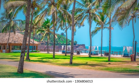 North Goa, India - Candolim beach from Taj Holiday resort with Aguada fort. Famous tourist summer vacations destination on the beach by Arabian Sea in Goa tropical climate with coconut palms.