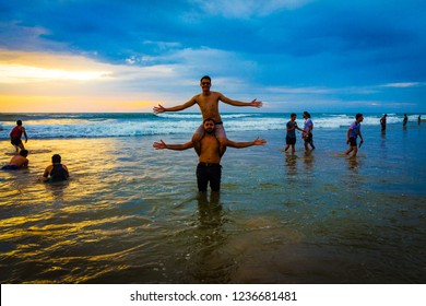 North Goa, Goa / India - October 20 2018: A duo of travellers posing on the Calangute beach during the sunset on the beach with clear blue sky. Fun at beach. Party at beach. Best beaches in India.