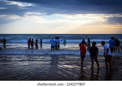 North Goa, Goa / India - October 20 2018: Tourists enjoying the sand, ocean and sunset on the Calangute Beach. Goa's biggest draw is undoubtedly its virtually uninterrupted string of golden-sand beach