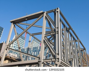 North Greenwich, London / UK - APR 28 2019: Steel frames and beams structure under construction against blue sky at Greenwich Peninsula redevelopment site.