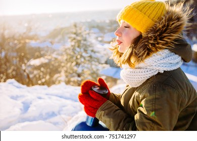 North hipster girl relaxing on the hill. Woman drinking hot tea from thermo cup and enjoing panorama city view. Happiness, winter holidays, tourism, travel and people concept.