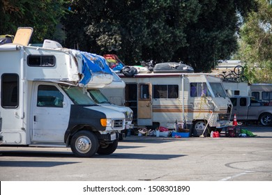North Hollywood, California / USA -  September 18, 2019: Recreational Vehicles parked at a homeless camp adjacent to the 170 freeway and the historical Valley Plaza shopping center.