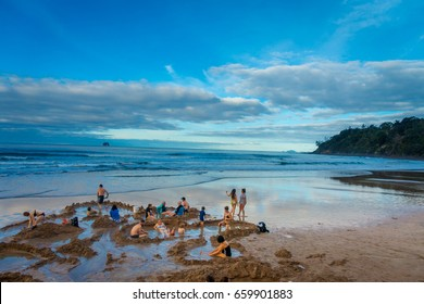 NORTH ISLAND, NEW ZEALAND- MAY 16, 2017: Tourists digging their own hot springs in Hot Water Beach, Coromandel. 130,000 annual visitors make it one of most popular attractions in Waikato region