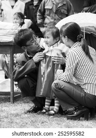 NORTH KOREA - MAY 1, 2012: Portrait of a Korean girl with her parents during the celebration of the Internationa Worker's Day in N.Korea, May 1, 2012. May 1 is a national holiday in 80 countries