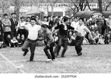 NORTH KOREA - MAY 1, 2012: Korean people jump over a skipping rope during the celebration of the International Worker's Day in N.Korea, May 1, 2012. May 1 is a national holiday in 80 countries