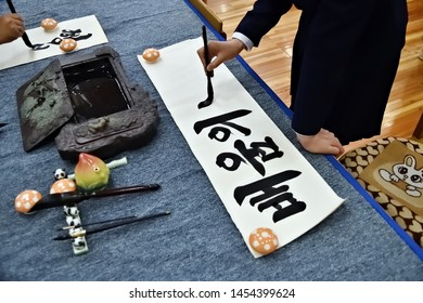 North Korea, Pyongyang - May 2, 2019: Hand of a girl writing black hieroglyphs on a white sheet of paper. Pyongyang Palace of schoolchildren. Extracurricular educational institution