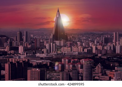 North Korea, Pyongyang. View of the city from above.Sunset over the city. Beautiful sun flare and pink red glow.