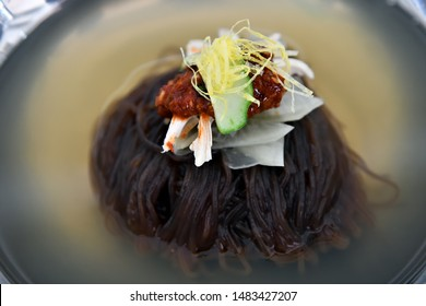 North Korean cuisine. Korean noodle dish. Naengmyeon or rraengmyon. Cold buckwheat noodles with water diluted with soy sauce and mustard. Also contains vegetables, egg and boiled meat