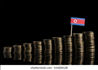North Korean flag with lot of coins isolated on black background