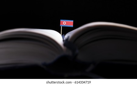 North Korean flag in the middle of the book. Knowledge and education concept.