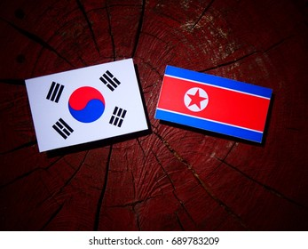North Korean flag with South Korean flag on a tree stump isolated
