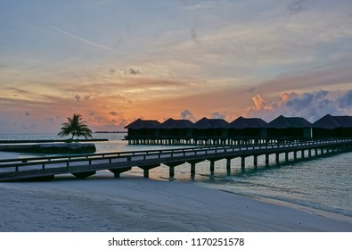 NORTH MALE, MALDIVES -6 JUL 2018- Sunset over the luxury over-the-water bungalows with thatched roofs at the Sheraton Maldives Full Moon Resort & Spa hotel on Furanafushi Island, North Malé Atol.
