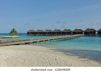NORTH MALE, MALDIVES -6 JUL 2018- View of expensive luxury over the water bungalows with thatched roofs at the Sheraton Maldives Full Moon Resort & Spa hotel on Furanafushi Island, North Malé Atol.