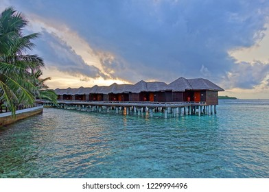 NORTH MALE, MALDIVES -6 JUL 2018- Sunset view of luxury over the water bungalows with thatched roofs at the Sheraton Maldives Full Moon Resort & Spa hotel on Furanafushi Island, North Malé Atol.