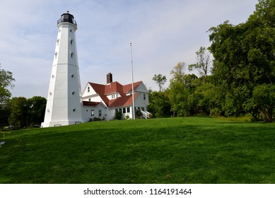 The North Point Lighthouse in Milwaukee Wisconsin on a sunny day with some light clouds.