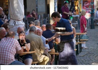 Düsseldorf, North Rhine-Westphalia / Germany - 08/24/2016: Man serving beer to people at outdoor tables, Zum Uerige Biergarten