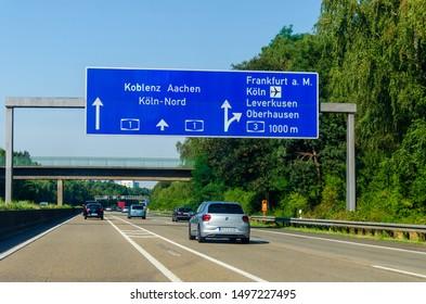 North Rhine-Westphalia, Germany - July 26, 2019: Road traffic on the German Highway (autobahn) A1 with road signs. Cars ride on the German autobahn.