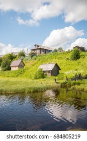 north Russian village Isady. Summer day, Emca river, old cottages on the shore, old wooden bridge and clouds reflections