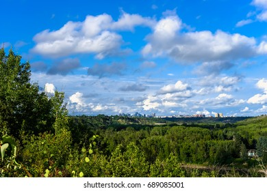 North Saskatchewan river Valley leading to downtown of the city of Edmonton with clouds and blue sky background