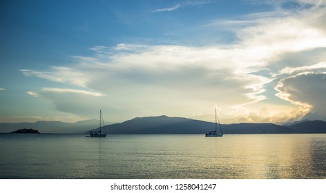 North sea bay panoramic landscape with two sail boats in calm water surface and mountain horizon background silhouettes in morning sun rise quiet time