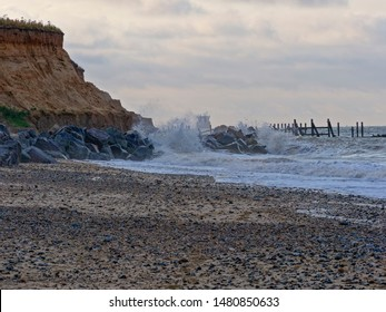 North Sea waves break against rocks protecting soft sand cliffs from erosion. Remains of a jetty lead out to sea and a ship is close inshore.