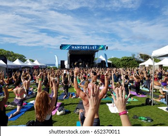 NORTH SHORE, HAWAII - FEBRUARY 26: Yogi move in yoga class a celebration of the power of yoga, community, music, nature outdoors  at Wanderlust yoga event on the North Shore, Hawaii February 26, 2017.