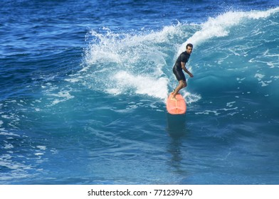 NORTH SHORE, OAHU, HAWAII - DECEMBER 7, 2017: An unidentified surfer catches a wave at Waimea Bay Beach Park located on the North Shore of Oahu.