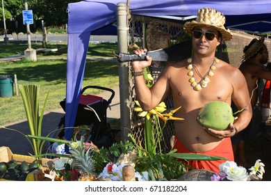 NORTH SHORE, OAHU, HAWAII - FEBRUARY 9, 2016: An unidentified Hawaiian man prepares to open a coconut at a juice and fruit stand across from Sunset Beach on the North Shore of Oahu.